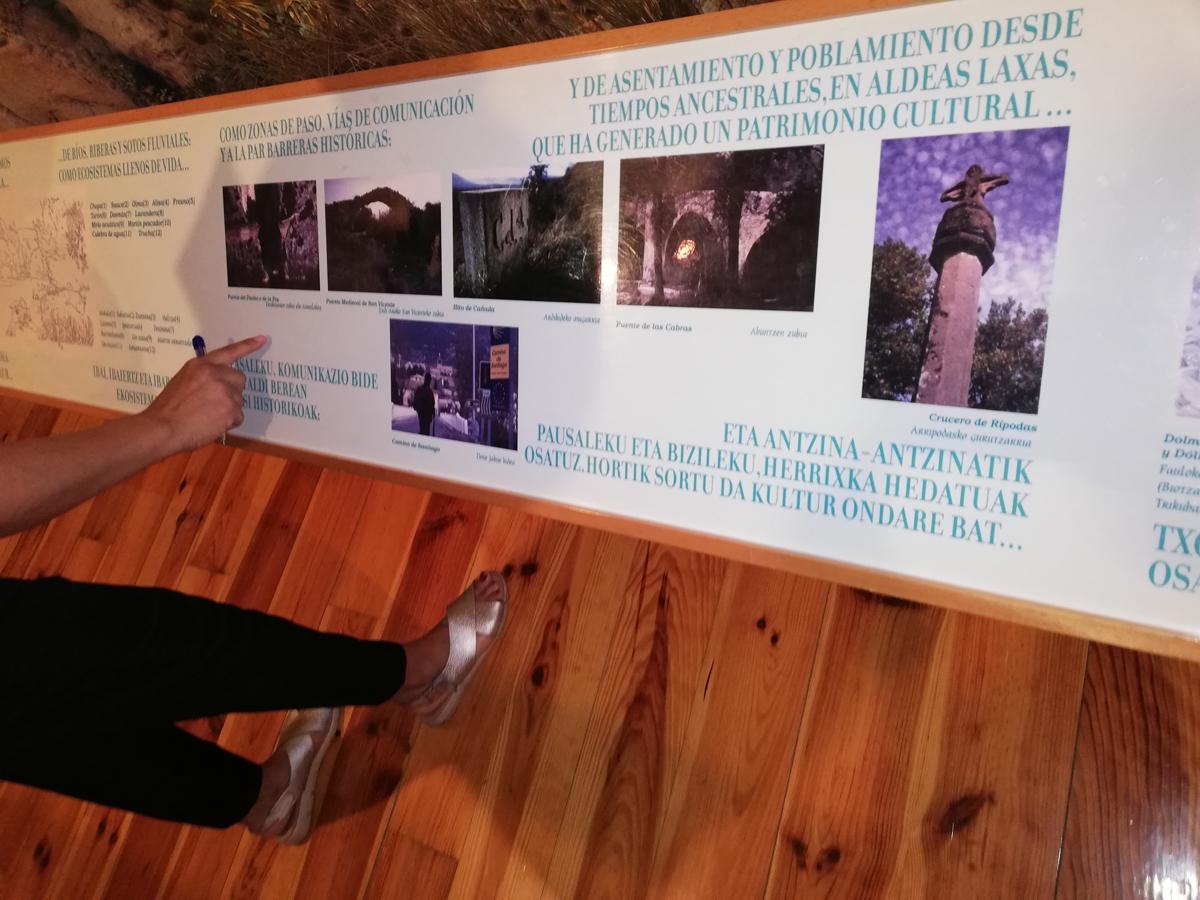 Fotografía de un panel horizontal con textos y fotos. Una mano señala el panel