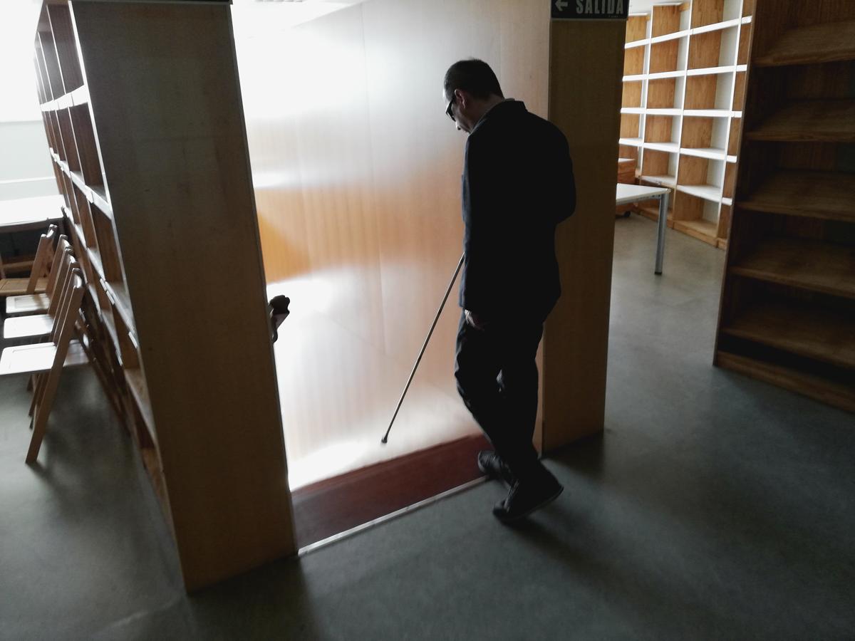 Foto de un hombre con gafas de sol y bastón blanco se dispone a bajar unas escaleras.