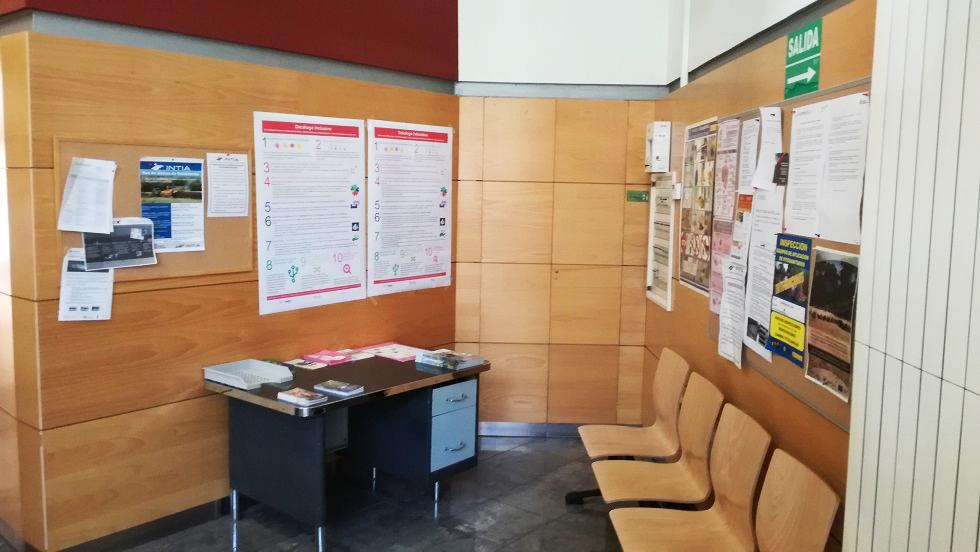 Dos posters con el decálogo inclusivo en euskera y castellano en la pared de una sala de espera de la oficina de Tudela, colgados en una pared de madera, cerca de otros folletos.