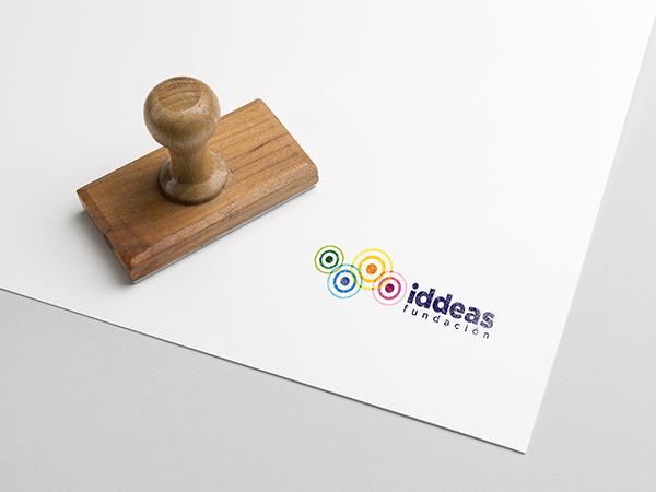 Un papel con el logotipo de Fundación Iddeas y un sello de madera