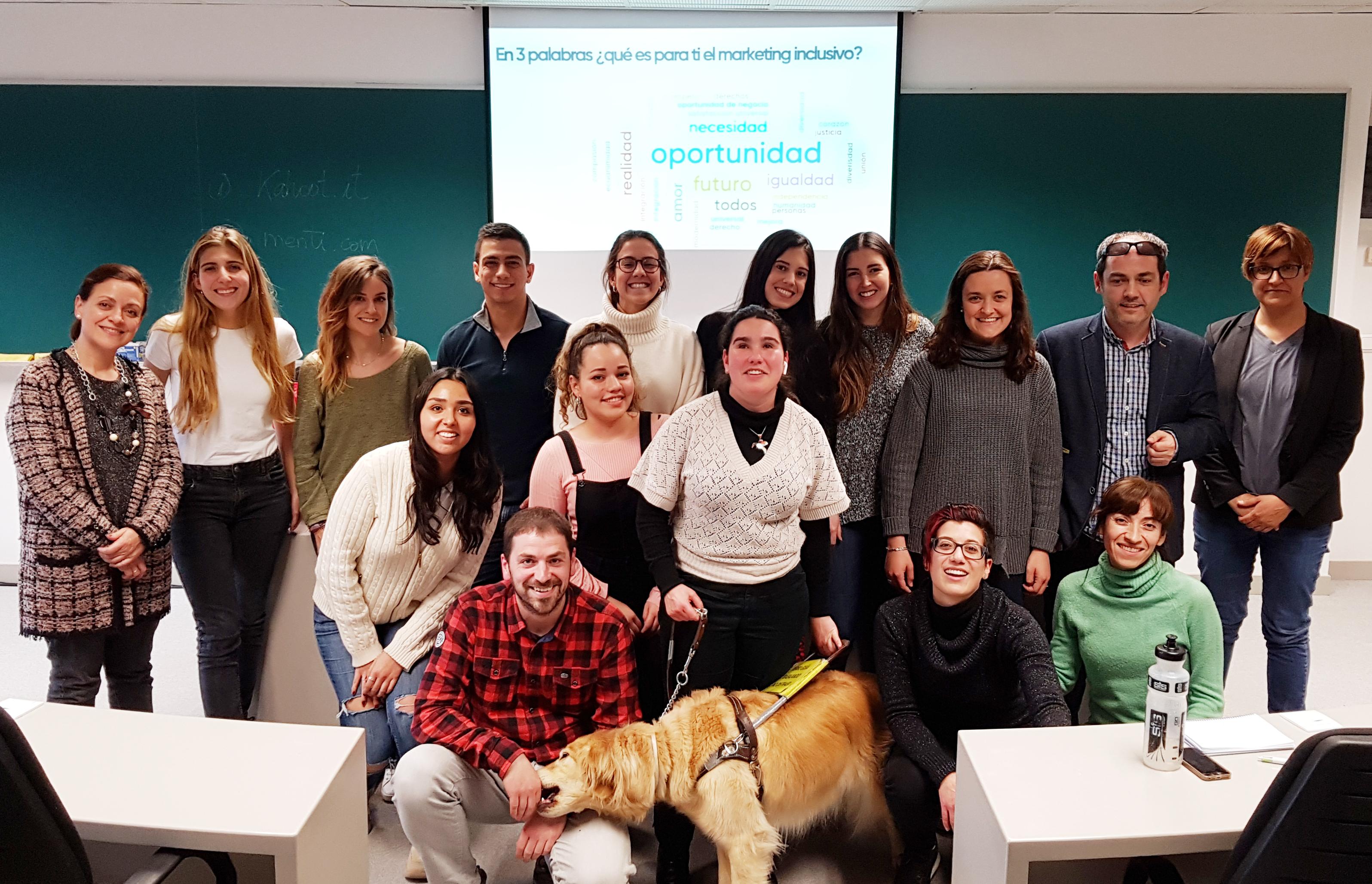 Foto final de grupo en el tercer Seminario de marketing inclusivo en la Universidad de Navarra. Unas 16 personas, con el perro-guía de Zuriñe de Anzola. Al fondo, la pantalla con las palabras que han dado los asistentes con las que resumen el marketing inclusivo. La más grande: oportunidad.