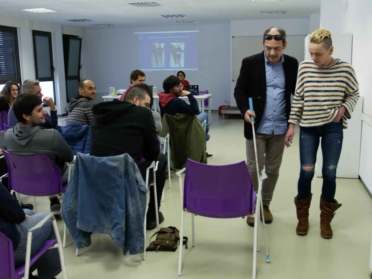 Imagen de Luis Casado, usuario de bastón blanco, enseñándole a una participante en un curso a guiar a una persona ciega.