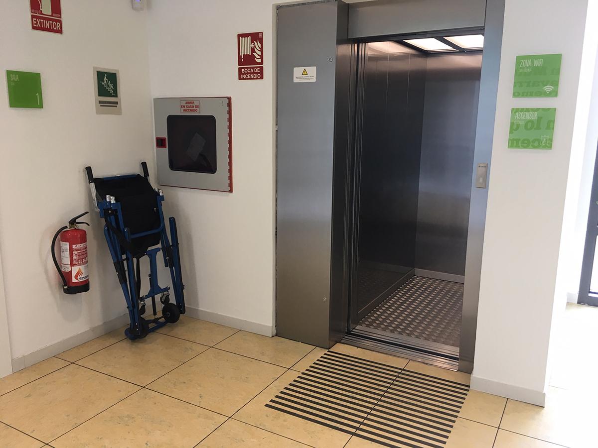 Uno de los ascensores de Mutua Navarra, frente al cual se han instalado unas bandas de advertencia para usuarios de bastón. Además, al estar cerca de las escaleras, a su lado se ha colocado una silla de evacuación para personas con problemas de movilidad