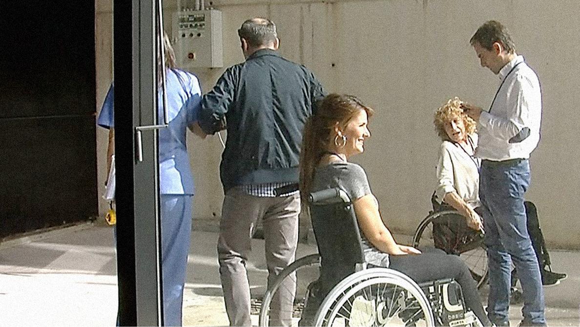 En el exterior de Mutua Navarra, dos mujeres en silla de ruedas y un hombre ciego siendo guiado por una trabajadora de Mutua Navarra