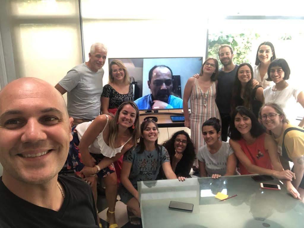 Selfie del equipo de Inter-cultura junto a la pantalla donde está Luis Casado.