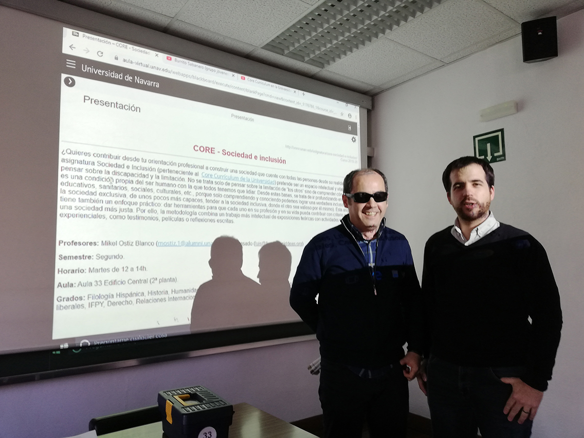 Foto de los profesores Luis Casado y Mikel Ostiz frente a la pantalla donde se proyecta la presentación de la asignatura Sociedad e inclusión, tomada el primer día de clase.