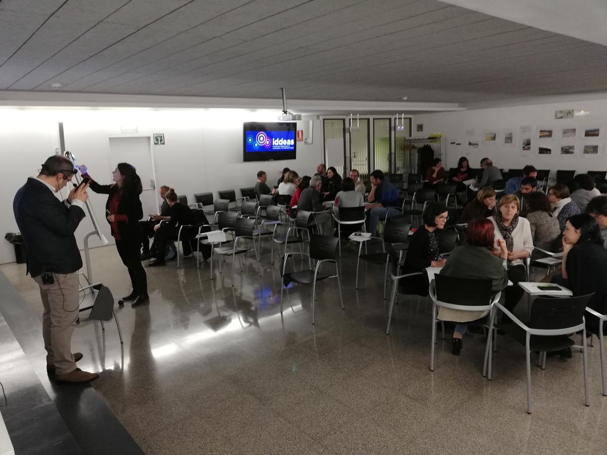 Imagen de la formación en el departamento de desarrollo rural del Gobierno de Navarra. Las personas están sentadas en grupos, mientras un ponente consulta su teléfono móvil y otra ponente escribe en una pizarra.