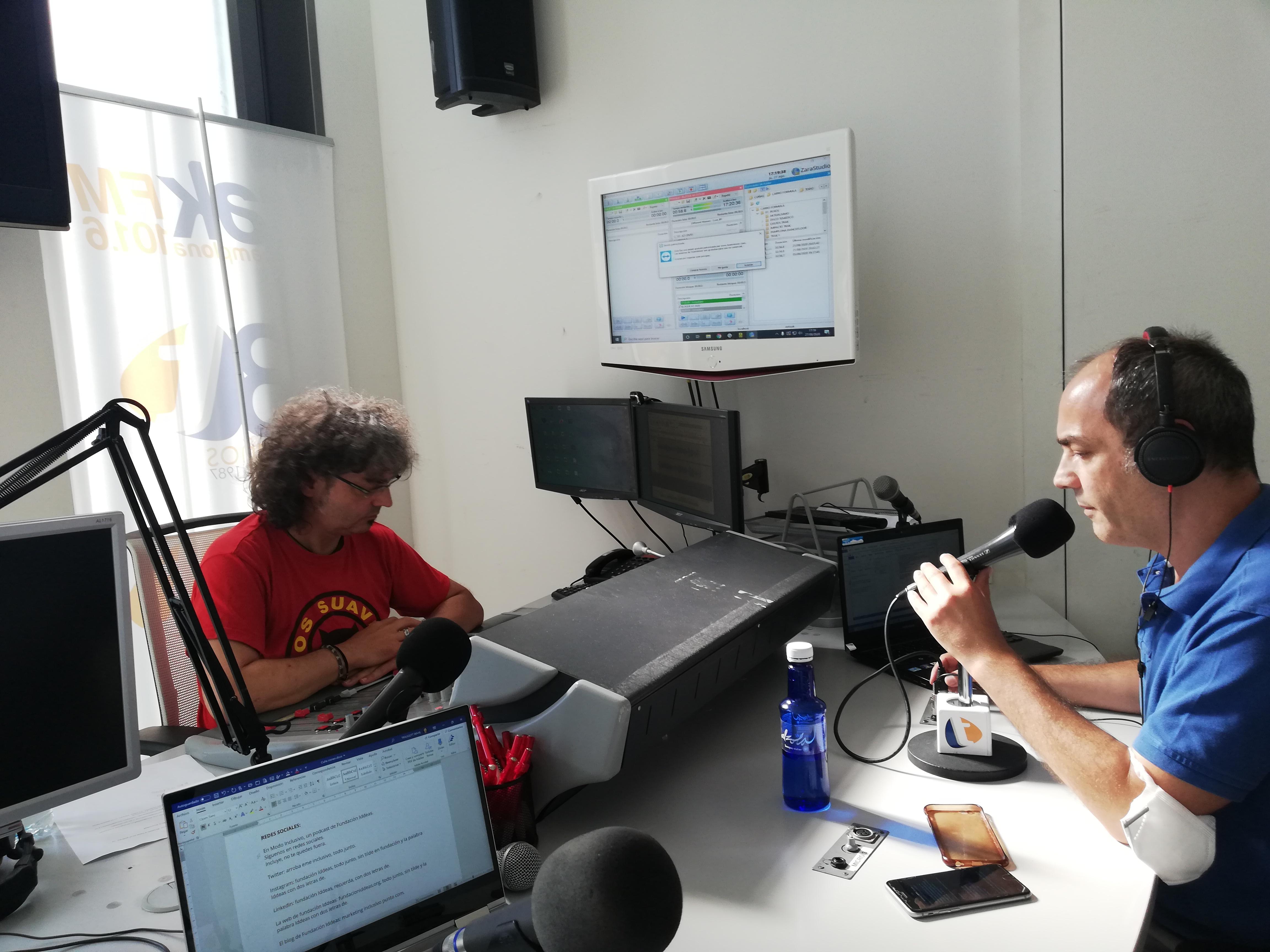 Imagen de Luis Casado hablando en el estudio. Frente a él, el técnico de sonido controla la grabación frente a varios monitores y una mesa de mezclas.